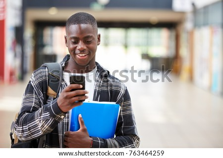 Male College Student Reading Text Message On Mobile Phone