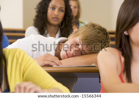 Male college student sleeping through a university lecture