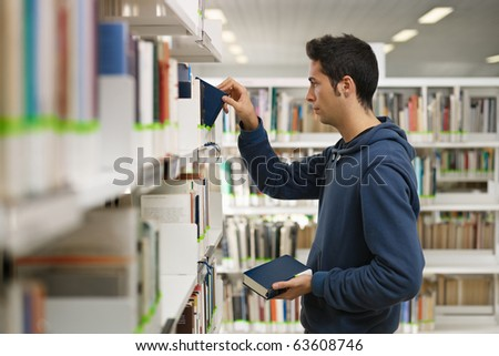 male college student taking book from shelf in library. Horizontal shape, side view, waist up