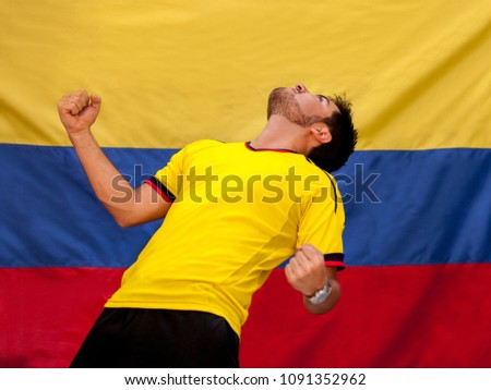 Male Colombian soccer fan celebrating with the Colombian flag in the back - Shutterstock ID 1091352962