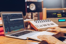 male composer, producer, arranger, song writer, musician hands arranging music on computer in home studio. music production concept