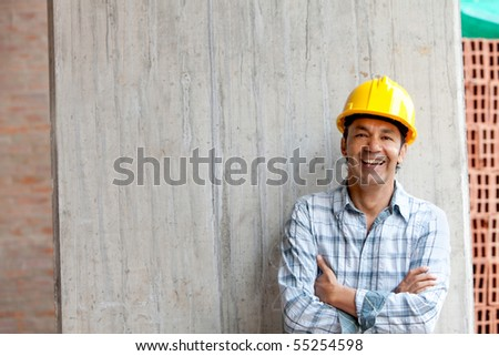 Male construction worker at a building site smiling
