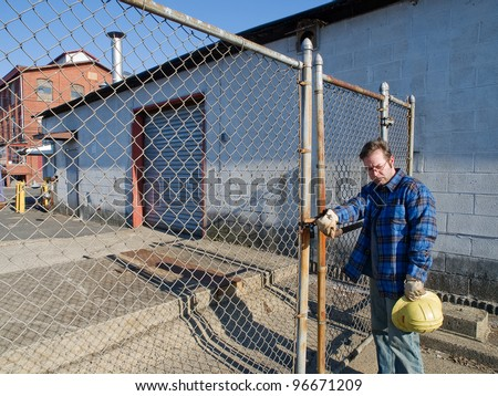 Male Construction Worker, forlorn, outdoors, out of work , locked out, factory