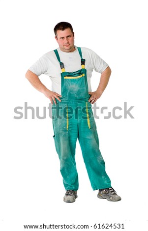 Male construction worker with dirty outfit looking at camera, arms on waist, isolated