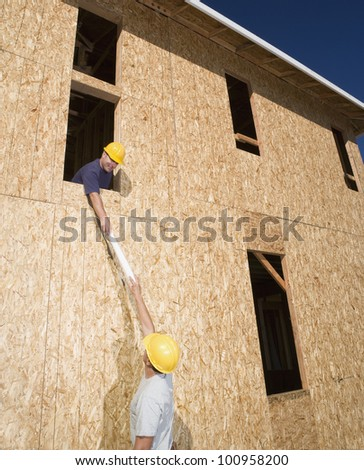 Male construction workers at construction site - stock photo