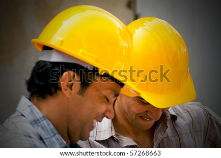 Male construction workers wearing helmets and smiling