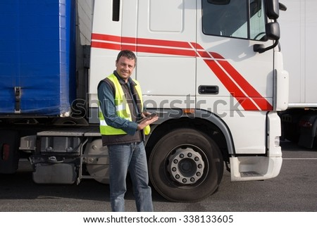 Male contractor on his tablet while standing by logging truck #338133605