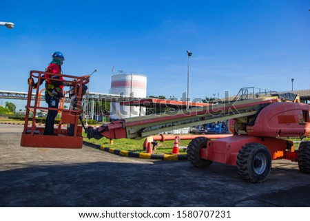 Male control boom lift in a industry working at high  inspection of pipeline oil