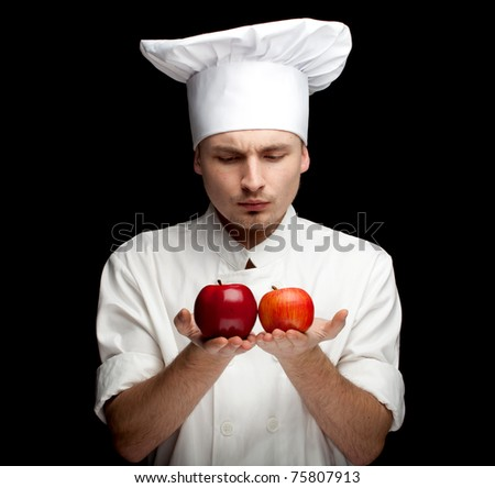 male cook in white uniform and hat with apples, black bckground