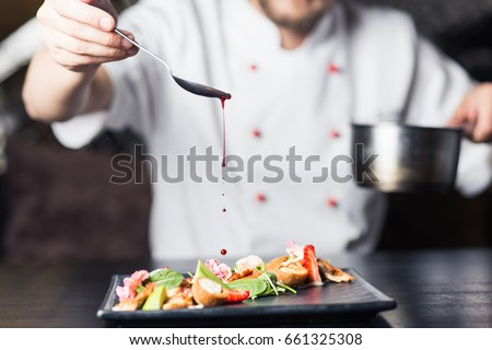 male cooks preparing meat in...