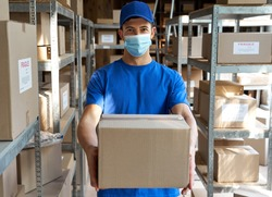 Male courier worker wearing uniform and face mask holding parcel box giving package to camera standing in stock warehouse, portrait. Fast express safe delivery during covid 19 pandemic concept.