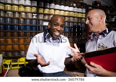 Male coworkers by shelves of colored inks in print shop