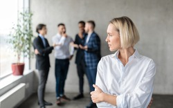 Male Coworkers Whispering Behind Back Of Unhappy Businesswoman Spreading Rumors And Gossips Standing In Modern Office. Sexism And Bullying Problem At Workplace Concept. Selective Focus
