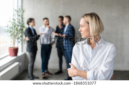 Male Coworkers Whispering Behind Back Of Unhappy Businesswoman Spreading Rumors And Gossips Standing In Modern Office. Sexism And Bullying Problem At Workplace Concept. Selective Focus Foto stock ©
