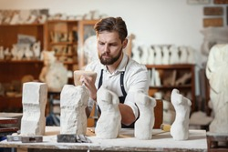 Male craftsman in working uniform makes a limestone copy of woman torso at the creative studio and show making process from start to finish.