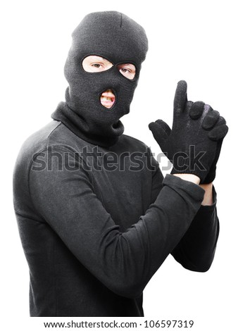 Male criminal in mask making a hand gun gesture in a depiction of a armed holdup or robbery isolated on white background