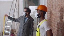 Male customer and foreman wearing protective mask checking wall redecoration in new apartment. Diverse foreman and builder in safety mask examining renovation of house