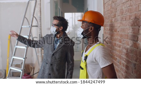 Male customer and foreman wearing protective mask checking wall redecoration in new apartment. Diverse foreman and builder in safety mask examining renovation of house Photo stock ©