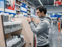 male customer buying spray paint can in the supermarket. He is reading what to buy. difficult decision. Various choice