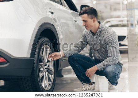 Male customer examining wheels and tires of a new car at the dealership. Handsome man choosing new car to buy at the showroom. Retail, rental service, consumerism concept