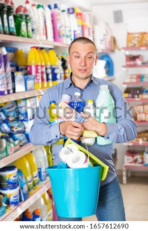 Male customer holding household chemistry with shopping list in  shop