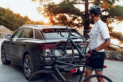 Male cyclist loading his bicycle on a rack of his crossover car