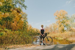 Male cyclist standing with bicycle on background of beautiful autumn landscape and looking into camera. A cyclist is on a bike ride through the autumn park. Outdoor activities.Cycling concept.