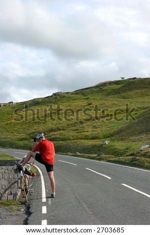 Male cyclist stopping for a rest on an uphill rural  mountain road. - stock photo