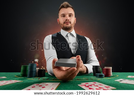 Male dealer at the casino at the table. Casino concept, gambling, poker, chips on the green casino table