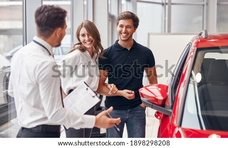 Male dealer with clipboard gesticulating and speaking with happy young man and woman near new vehicle while working in car showroom
