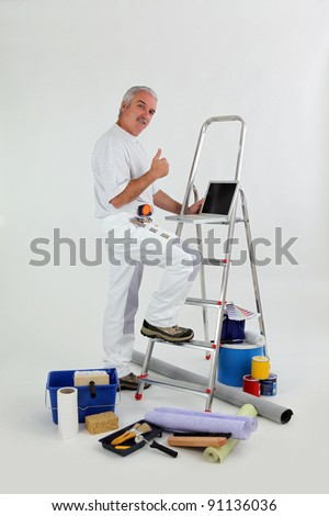 Male decorator with ladder giving thumbs-up