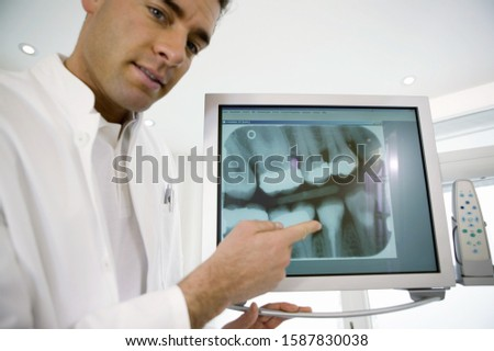 Male dentist pointing at dental x-ray