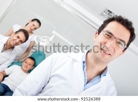 Male dentist smiling with his team at his practice