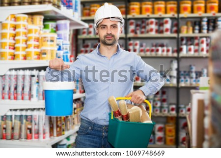 Male designer in helmet is holding paint and all instruments for redecorate room in the store