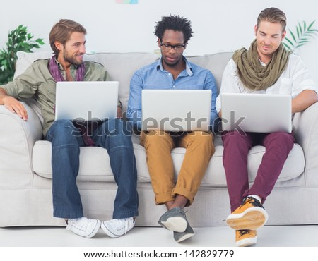 Male designers working together with laptops sit on a sofa