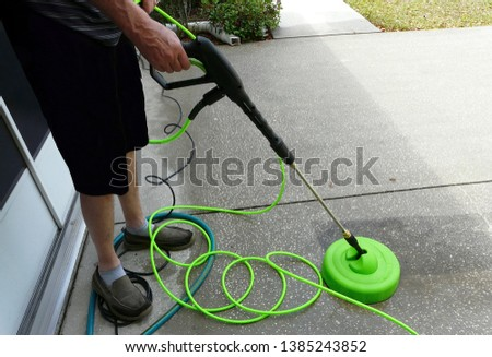 Male do-it-yourselfer homeowner is pressure washing the driveway in front of his house with a surface cleaner attachment. #1385243852