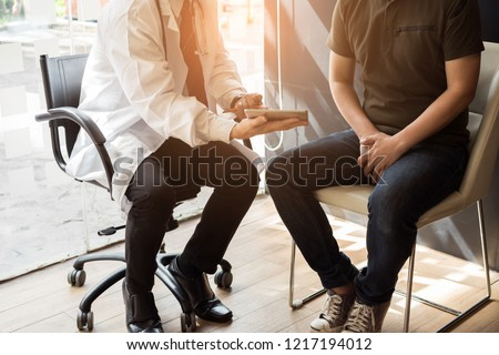 Male doctor and prostate cancer patient are discussing about prostate cancer test report. Testicular cancer and prostate cancer concept.