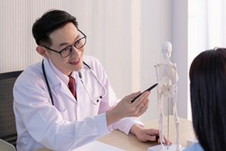 Male doctor explaining the spine to a patient in office. Physiotherapist shows the problem areas on the human skeleton anatomical model to patient. Doctor showing anatomical spine to patient.