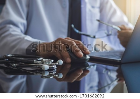Male doctor hand using wireless mouse, browsing medical information on laptop computer with stethoscope on the desk. Medic tech, telehealth , online medical, teleconference or telemedicine concept.
