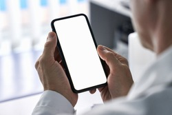 Male doctor holding cell phone in hands using blank white mockup screen technology ehealth mobile app for medical healthcare telemedicine ads, e telehealth online applications. Over shoulder view