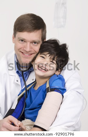 Male doctor in early forties holding five year old disabled patient during office visit