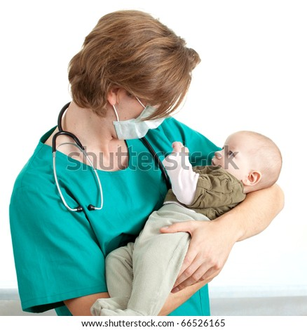 male doctor in green uniform and protective medical mask examining baby boy
