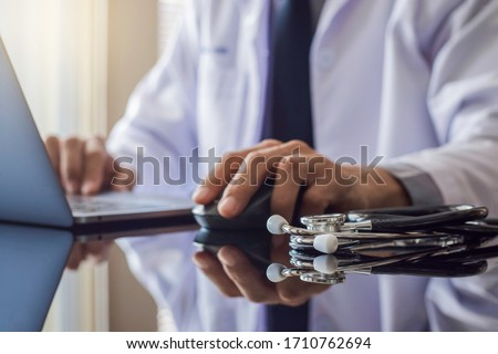 Male doctor in white coat, hand using wireless mouse and work on laptop computer with stethoscope on the desk at office. Meditech, telehealth , online medical, ehr, emr or telemedicine concept.