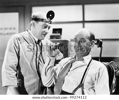 Male doctor listening to a man who is explaining something with his fingers - stock photo