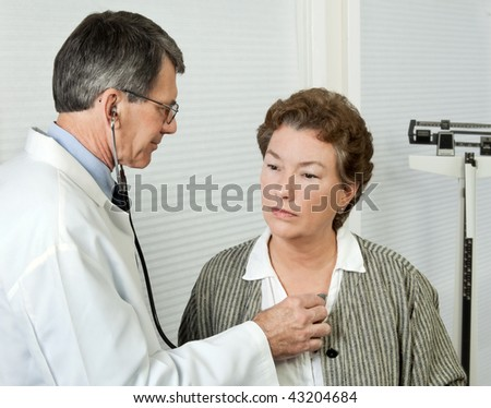 Male doctor listens to mature woman\'s heart during an office visit.