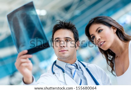 Male doctor looking an x-ray  with a patient
