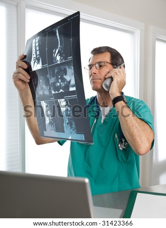 Male doctor on the phone in a hospital or office clinic, examining spinal scans and discussing his findings.