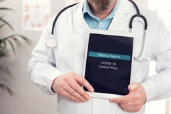 Male doctor showing medical covid-19 corona virus report on a tablet