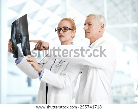 Male doctor shows the problem areas on a X-ray to his colleagues at private clinic.