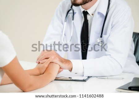 Male doctor soothes a female patient in hospital office while holding the patients hands. Healthcare and medical service.